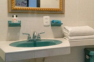 Lavabo, amenidades, toallas en baño de habitación