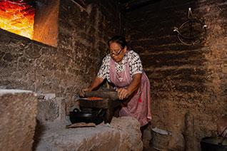 Mujer utilizando un metate para moler el chocolate